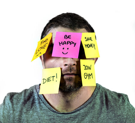young man overwhelmed and overworked in stress with face full of  notes stuck covering him with reminders and resolutions isolated on white background Foto de archivo