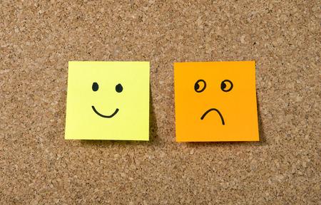 cara triste: dos notas pegadas a bordo de corcho o mensaje con smiley y expresión triste cara de dibujos animados en la felicidad frente a la depresión y la sonrisa contra el concepto de la adversidad