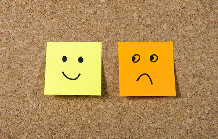 painted face: two  notes stuck on corkboard or message board with smiley and sad cartoon face expression in happiness versus depression and smile against adversity concept
