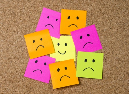 depression: smiley cartoon face expression on yellow  note surrounded by sad and depressed faces on cork message board in happiness versus depression and smile against adversity concept