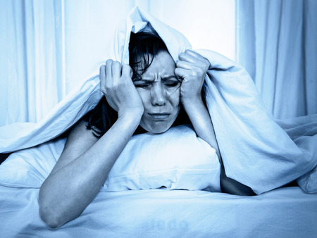 young moody woman in bed suffering stress with her insomnia problem and sleeping disorder or hangover covering with blanket and bedclothes on studio blue lighting photo