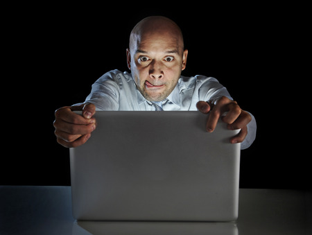 young addict man alone at night sitting watch computer laptop