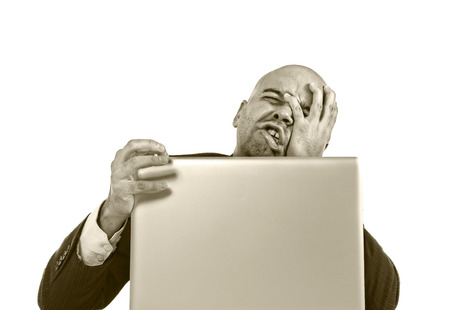 internet porn: businessman in crisis and stress at computer laptop holding monitor Stock Photo