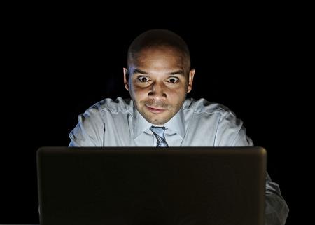 jonge aantrekkelijke zakenman alleen 's nachts zitten horloge computer laptop Stockfoto