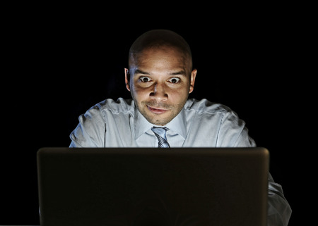 lascivious: young attractive businessman alone at night sitting watch computer laptop