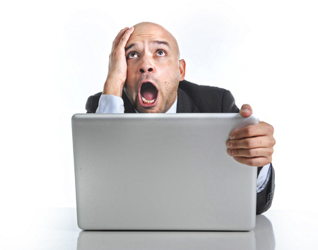 excited desperate businessman in stress at computer laptop holding monitor photo