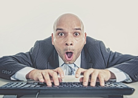 internet porn: young businessman typing on computer keyboard with funny face expression on watching porn online and internet chat and social network addiction concept isolated on white background