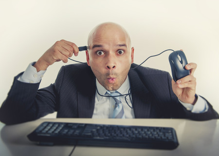 businessman plugging computer mouse to his head in funny face expression on technology dependence and internet addiction concept isolated on white background