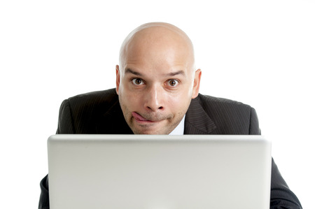 internet porn: young businessman typing on computer keyboard with funny face expression on watching internet porn online or making money gambling on line isolated on white background