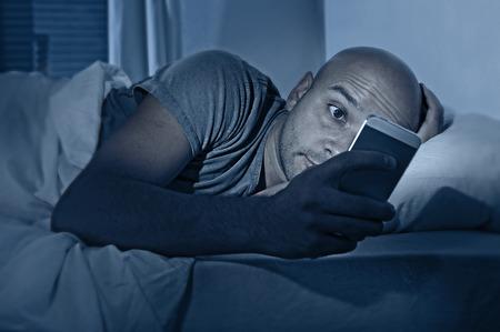 침대에서 밤에 깨어있는 젊은 휴대 전화 중독자 남자, 채팅 유혹과 인터넷 중독과 모바일 남용 개념에 문자 메시지를 전송하는 스마트 폰을 사용