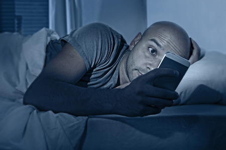 young cell phone addict man awake at night in bed using smartphone for chatting, flirting and sending text message in internet addiction and mobile abuse concept Stock Photo