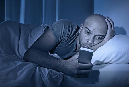 チャット、いちゃつく、インターネット中毒とモバイル虐待概念でテキスト メッセージを送信するスマート フォンを使用してベッドで夜に目がさめ