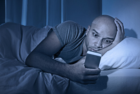 addiction alone: young cell phone addict man awake at night in bed using smartphone for chatting, flirting and sending text message in internet addiction and mobile abuse concept Stock Photo