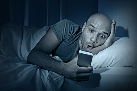 cell phone addiction: young cell phone addict man awake at night in bed using smartphone for chatting, flirting and sending text message in internet addiction and mobile abuse concept Stock Photo