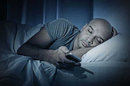 cell phone addiction: young cell phone addict man sleeping at night in bed while using smartphone for chatting, flirting and sending text message  in internet addiction and mobile abuse concept