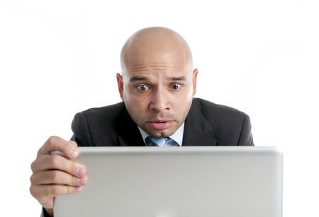 internet porn: excited desperate businessman in stress at computer laptop holding monitor watching online finances drop down or loosing money online gambling isolated on white background Stock Photo