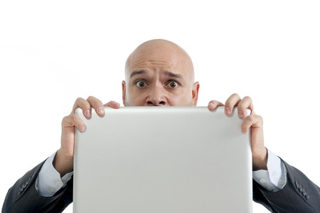 excited desperate businessman in stress at computer laptop holding monitor watching online finances drop down or loosing money online gambling isolated on white background photo
