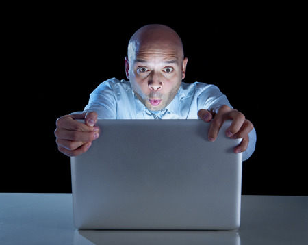 internet porn: excited businessman alone at night sitting at computer laptop watching porn or online gambling isolated on black