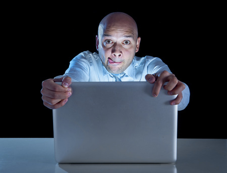 excited businessman alone at night sitting at computer laptop watching porn or online gambling isolated on black