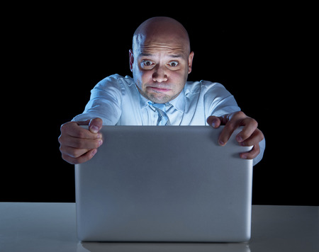 addicted: excited businessman alone at night sitting at computer laptop watching porn or online gambling isolated on black Stock Photo