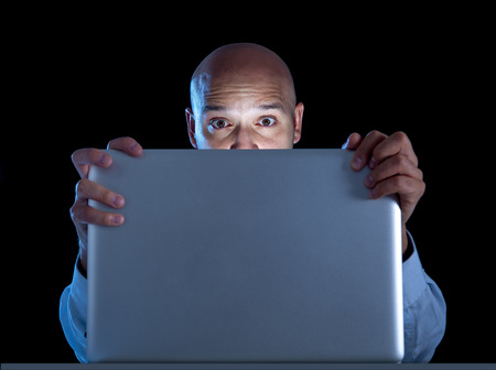 excited businessman alone at night sitting at computer laptop watching porn or online gambling isolated on black Stock Photo