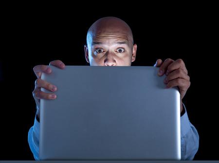 один рады бизнесмен ночью сидит на компьютере, ноутбуке за просмотром порно или азартные игры онлайн, изолированных на черном