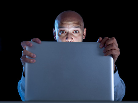 lascivious: excited businessman alone at night sitting at computer laptop watching porn or online gambling isolated on black