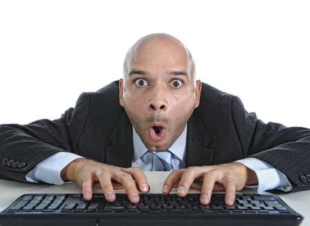 internet porn: young businessman typing on computer keyboard with funny face expression on watching porn online and internet chat