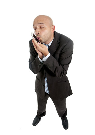 happy young friendly businessman using compulsively cell phone kissing his handy in social network