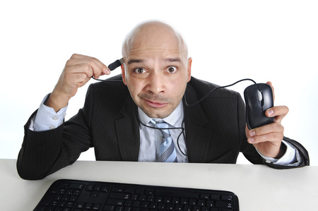 surprised face: businessman plugging computer mouse to his head in funny face expression Stock Photo