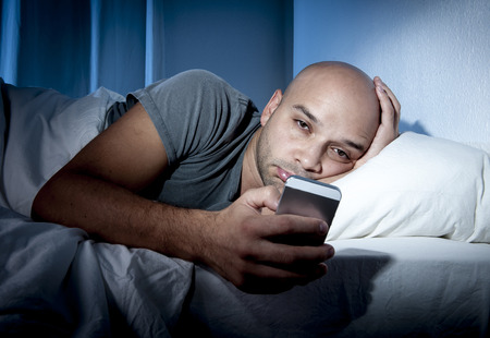 Jonge mobiele telefoon verslaafde man wakker 's avonds laat in bed met behulp van smartphone om te chatten Stockfoto - 32786050