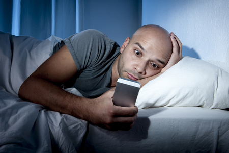 cell phone addiction: young cell phone addict man awake late at night in bed using smartphone for chatting