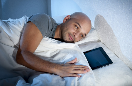 sleeping pad: happy young internet addict man awake late at night in bed sleeping with digital pad Stock Photo