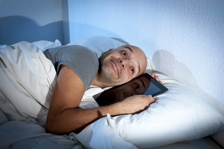 happy young internet addict man awake late at night in bed sleeping with digital pad photo