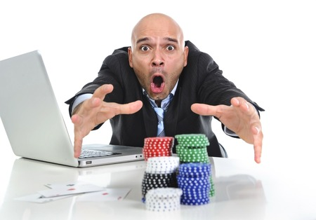 desperate addict businessman on computer laptop winning and loosing money betting on internet poker with cards and chips on online gambling addiction isolated on white photo
