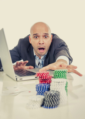 desperate addict businessman on computer laptop loosing lots of money betting on internet poker with cards and chips on online gambling addiction isolated photo
