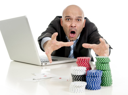 desperate addict businessman on computer laptop loosing lots of money betting on internet poker with cards and chips on online gambling addiction isolated on white photo