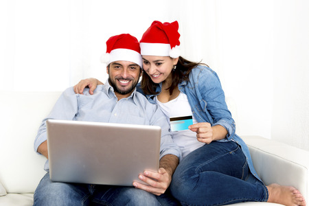 young attractive Hispanic couple in love sitting together on sofa couch at home living room with computer laptop shopping online Christmas presents with credit card on internet photo