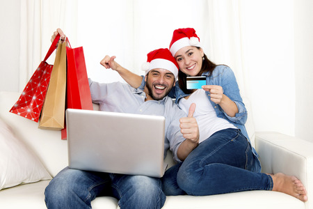 young attractive Hispanic couple in love together on sofa couch at home with computer laptop holding shopping bags purchasing online Christmas presents with credit card on internet photo