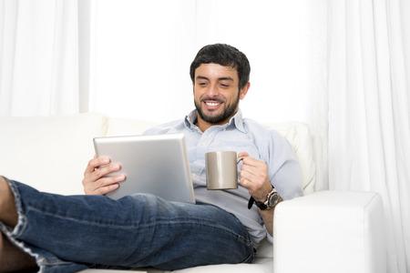 relajado: Joven hombre hispánico atractivo feliz en casa acostado en el sofá con la tableta digital o almohadilla relajado beber café disfrutando de navegar por Internet viendo películas en línea