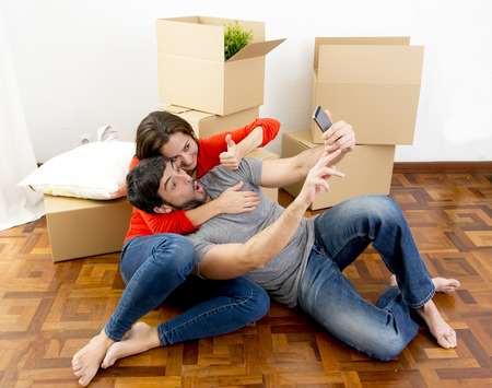 young happy couple moving together in a new house , flat or apartment unpacking cardboard boxes home belongings having fun taking selfie video and picture