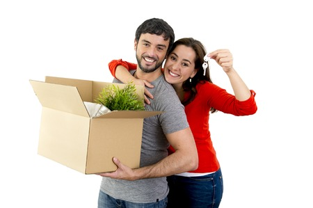 belongings: young happy Hispanic couple moving together in a new house , flat or apartment carrying cardboard boxes home belongings smiling in housing and real state concept Stock Photo