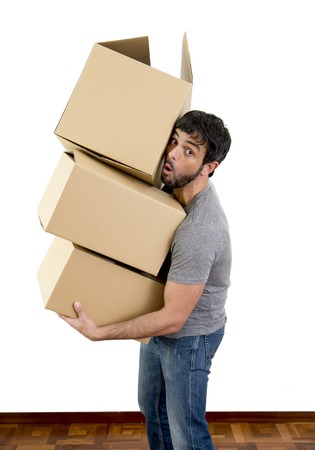 young happy Hispanic single man moving alone in a new house , flat or apartment carrying pile of cardboard boxes home belongings in housing and real state concept