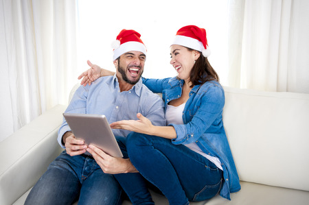 young attractive Hispanic couple in love together on sofa couch wearing Santa hat with digital tablet computer smiling happy purchasing online Christmas presents on internet photo