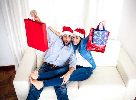 young happy couple wearing Santa hat and casual clothes on Christmas holding shopping bags with presents and gifts sitting on couch at home smiling and loving photo