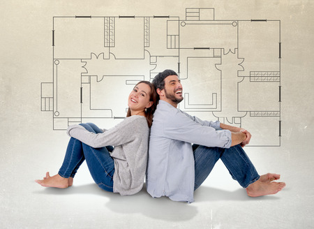 Young attractive couple in love happy together thinking and imaging blueprints , floor plan and design of new house, home, flat or apartment in real state concept Archivio Fotografico