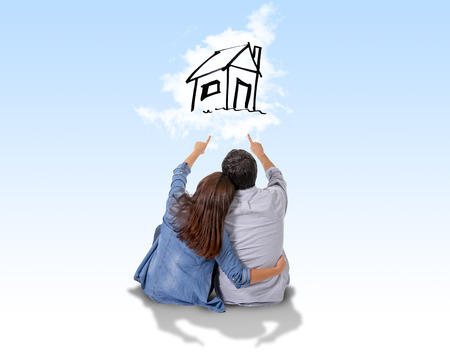 Jonge aantrekkelijke en moderne paar in liefde lachend gelukkig samen zittend op de vloer denken en de beeldvorming van hun nieuwe huis, flat of appartement in werkelijke toestand concept
