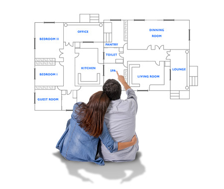 Young attractive couple in love happy together planning and pointing  blueprints , floor plan and design of new house, home, flat or apartment in real state concept