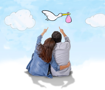 stork: young attractive Hispanic couple on floor, pregnant woman sitting together handsome husband and flying stork bringing baby in pregnancy and family growth concept