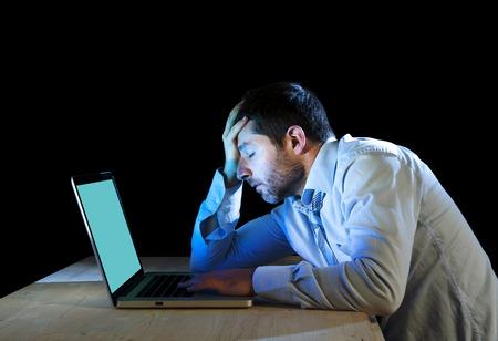 jonge beklemtoonde zakenman werken met laptop computer in frustratie, depressie, werkstress problemen en wanhoop concept geïsoleerd op zwarte achtergrond